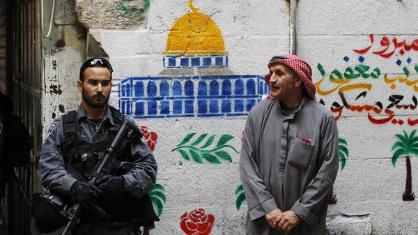 An Israeli policeman (L) stands next to a Palestinian man in Jerusalem's old city.