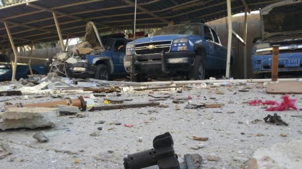 Police vehicles are parked next to debris in the Anbar province town of Hit, October 6, 2014.