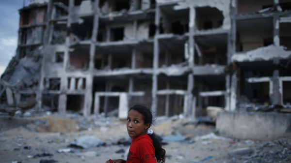 A Palestinian girl walks past residential buildings that witness said were shelled during the seven-week Israeli offensive, in the northern Gaza Strip.