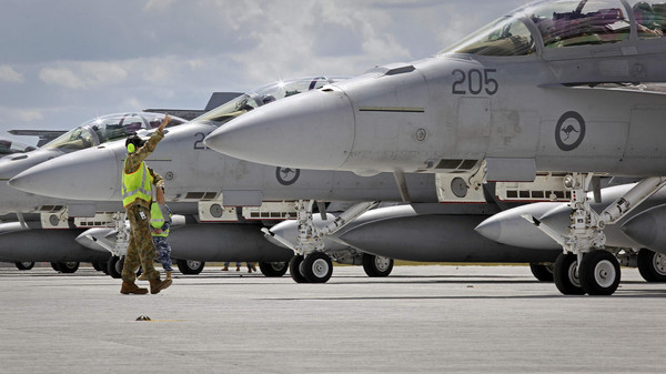 Ground staff assist crews of Royal Australian Air Force (RAAF) F/A-18F Super Hornets as they prepare to take-off from RAAF Base Amberley in Queensland in this handout picture taken on September 21, 2014 and released by the Australian Defence Force September 22, 2014.