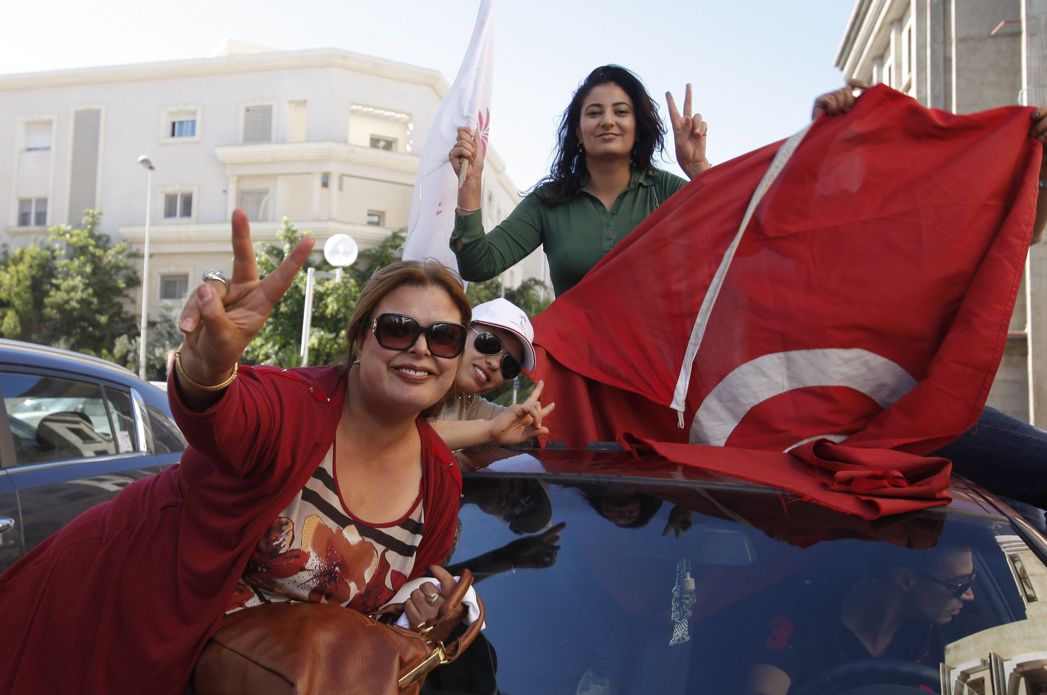 Supporters of the Nida Tounes (Call of Tunisia) secular party movement wave flags and shout slogans outside Nidaa Tounes headquarters in Tunis Oct. 28, 2014.