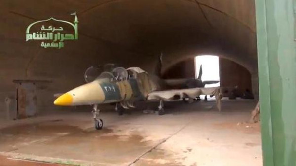 A picture shows a Syrian fighter jet in a hangar after rebels captured Jarrah airfield in Aleppo Province.