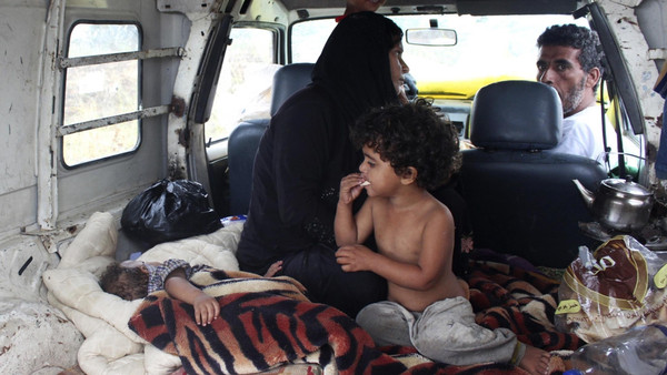 Syrian refugees take shelter inside a van after their makeshift tent was damaged by heavy rain in Halba, northern Lebanon, Sept. 28, 2014.