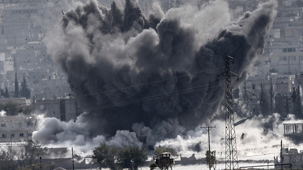 A picture taken from the Turkish border near the southeastern village of Mursitpinar, in the province of Sanliurfa shows smoke billowing after a jet fighter hit Kobani, also known as Ain al-Arab, on October 28, 2014.