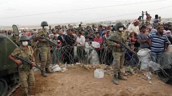 Turkish soldiers stand guard as Syrian Kurdish refugees wait behind the border fences to cross into Turkey near the southeastern town of Suruc in Sanliurfa province.