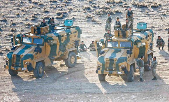 Turkish soldiers are seen atop and around armoured vehicles near the Mursitpinar border crossing on the Turkish-Syrian border in the southeastern town of Suruc in Sanliurfa province on Wednesday.