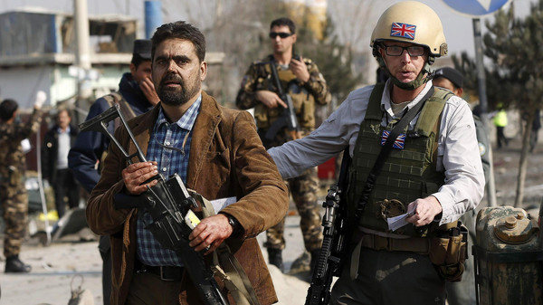 A British security official (R) escorts a survivor from the wreckage of a British embassy vehicle after a suicide attack in Kabul, November 27, 2014.