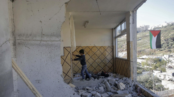 A Palestinian boy, relative of Abdel-Rahman Shaloudi, stands on rubble in Shaloudi's destroyed home in East Jerusalem. Israel destroyed the home Shaloudi, who last month ran over and killed two people at a tram stop.