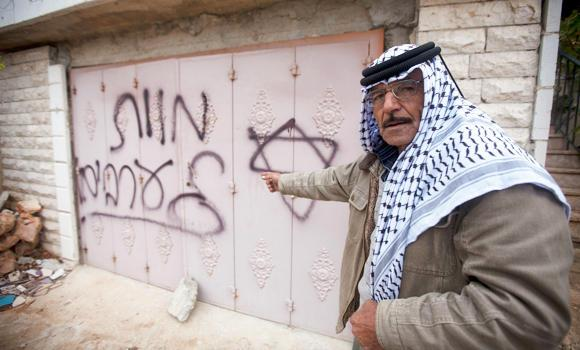 "A Palestinian man points to Hebrew graffiti reading ""Death to the Arabs"" following an arson attack in Khirbet Abu Falah, northeast of the West Bank city of Ramallah, on Sunday."