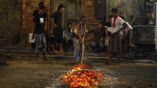 A Shiite Muslim prepares hot coals before others walk on it, during a ceremony ahead of the coming Ashura, at a mosque in central Yangon, November 11, 2013.