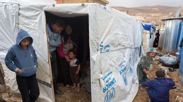 A Syrian refugee family stands near a tent damaged by heavy rains at the Al-Nihaya camp in the eastern Lebanese town of Arsal on Oct. 23, 2014.