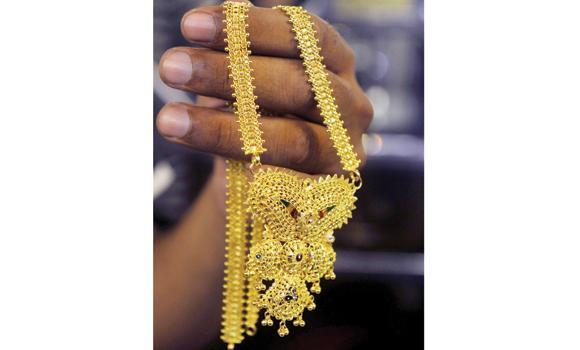 A jewelry shop owner shows a piece of gold jewelry to a customer in Kolkata.