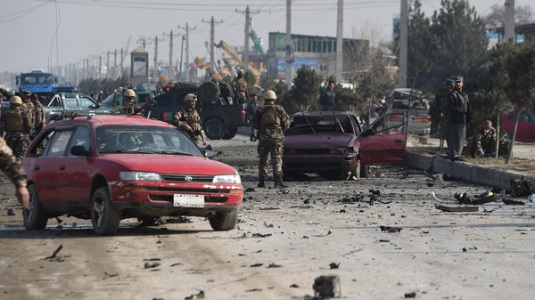 Afghan intelligence personnel inspect the site of a suicide attack on a British embassy vehicle along the Kabul-Jalalabad road in Kabul on Nov. 27, 2014.
