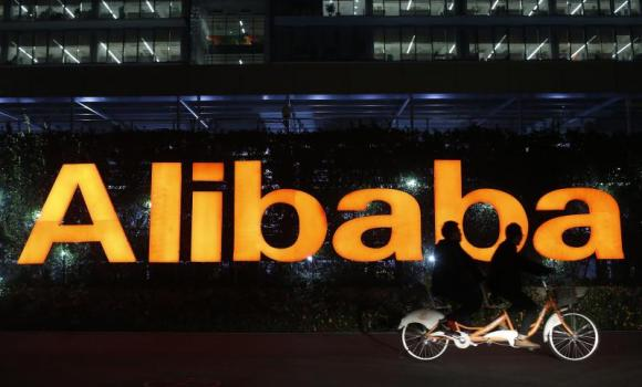 People ride a double bicycle past a logo of The Alibaba Group at the company's headquarters on the outskirts of Hangzhou, Zhejiang province.