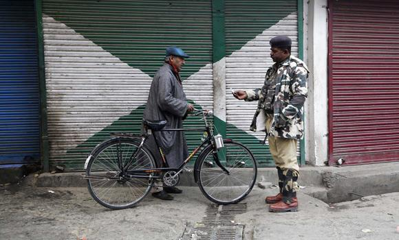 An Indian paramilitary soldier checks the identity of a civilian during curfew in Srinagar, India, on Nov. 4, 2014. An Indian military court on Thursday sentenced seven soldiers to life in prison for killing three Kashmiri youths.