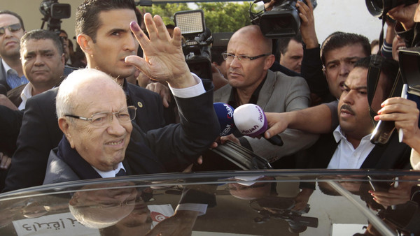 Beji Caid Essebsi (L), leader of Tunisia's secular Nidaa Tounes party and a presidential candidate, gestures after casting his vote at a polling station in Tunis Nov. 23, 2014.