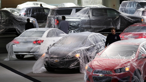 Vehicles are covered with protective wrap as workers prepare the General Motors automakers display ahead of the media preview of the North American International Auto Show at Cobo Center in Detroit, Michigan .