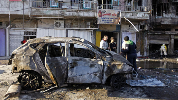 People gather at the site of a car bomb attack in Baghdad's al-Sinaa district Nov. 9, 2014.
