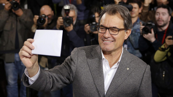 Catalan President Artur Mas holds up his ballot while voting in a symbolic independence vote in Barcelona, November 9, 2014.