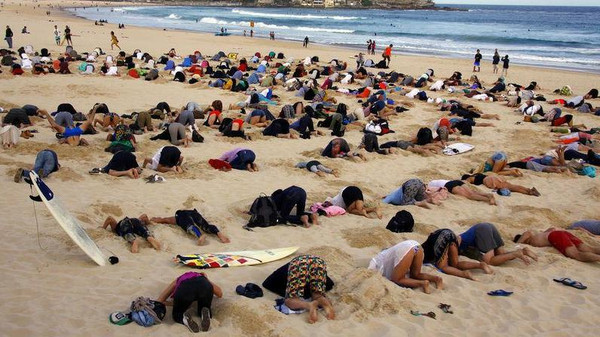 A group of around 400 demonstrators participate in a protest by burying their heads in the sand at Sydney's Bondi Beach Nov. 13, 2014.