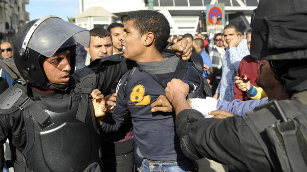 Egyptian police detain a supporter of the Muslim Brotherhood during clashes in Alexandria on January 23, 2014.
