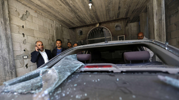 Fayez Abu Eitta (L), a Fatah leader in Gaza, speaks on the phone as he inspects the damage to his car in the parking lot of his home in Beit Lahya, northern Gaza Strip on Nov. 7, 2014.