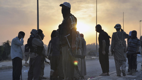 Fighters of the Islamic State of Iraq and Syria (ISIS) stand guard at a checkpoint in the northern Iraq city of Mosul.