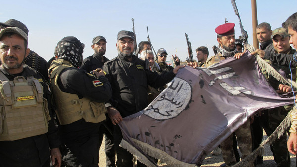 Iraqi Shiite fighters hold an Islamist State flag, which they pulled down from the frontlines after taking control of Saadiya in Diyala province from Islamist State militants, November 24, 2014.