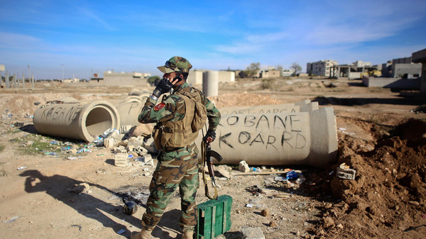 November 18, 2014, Kurdish Peshmerga fighter talking on the phone during fighting against ISIS in the Syrian border town of Ain al-Arab. US-led air strikes hit jihadist positions in the north and east of Syria, the Syrian Observatory for Human Rights said.