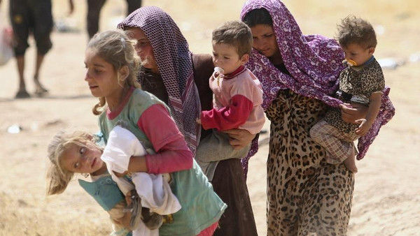 Displaced people from the minority Yazidi sect walk towards the Syrian border.