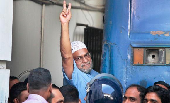 Mir Quasem Ali, a senior leader of the Bangladesh's largest Islamist party Jamaat-e-Islami shows victory sign as he enters a police van after a special tribunal sentenced him to death in Dhaka on Sunday.