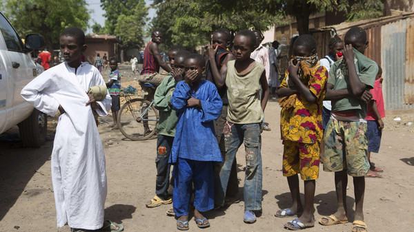 Children watch as health workers spray disinfectants at a mosque in Bamako November 14, 2014. A local government official said the body of a Guinean imam, suspected of dying from the Ebola virus on Oct. 27, was washed at the mosque before his funeral.