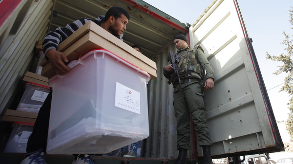 Polling agents lift a box of votes in a military truck to be distributed to the polling stations in Beja November 22, 2014.