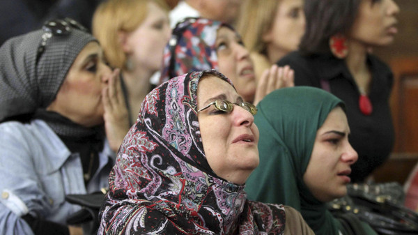 Relatives of detained activists cry and pray for them as the activists stand trial at a court in Cairo.