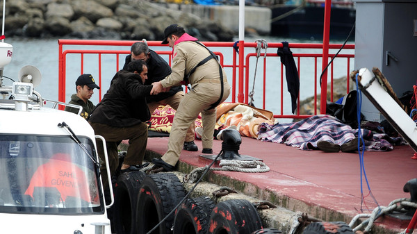 Rescue officials assist a survivor while the bodies of illegal migrants lie on the ground in Istanbul on November 3, 2014, after a boat carrying illegal migrants sank.