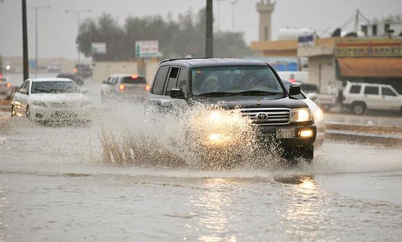 A car drives through a rain soaked road in Riyadh