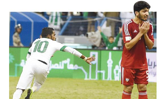 Saudi Arabia's footballer Nawaf Al-Abid, left, celebrates after scoring their first goal as the UAE's Amer Abdulra