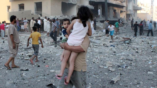 A man carries two children away from the scene of an August 7 explosion in the northern Syrian city of Raqqa.