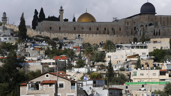 The Dome of the Rock and al-Aqsa mosque are seen in background as an Israeli flag flutters from atop a home of Jewish settlers in Silwan, a mostly Palestinian district abutting the Old City, Nov. 3, 2014.