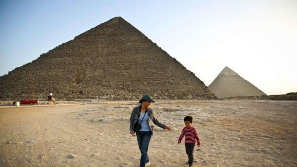 A picture taken on November 9, 2014, shows tourists walking past the pyramids of Menkaure (L) and Khafre (R) in Giza, on the outskirts of Cairo.
