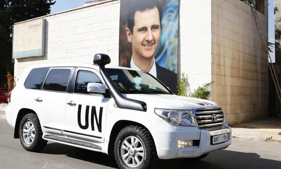 A poster of Syrian President Bashar al-Assad adorns a wall as the vehicle of United Nations special envoy for Syria Staffan de Mistura leaves his hotel on Sunday in Damascus. The Syrian Observatory for Human Rights said Sunday that unidentified attackers murdered five nuclear energy engineers who worked in the scientific research center near the neighborhood of Barzeh in northern Damascus.