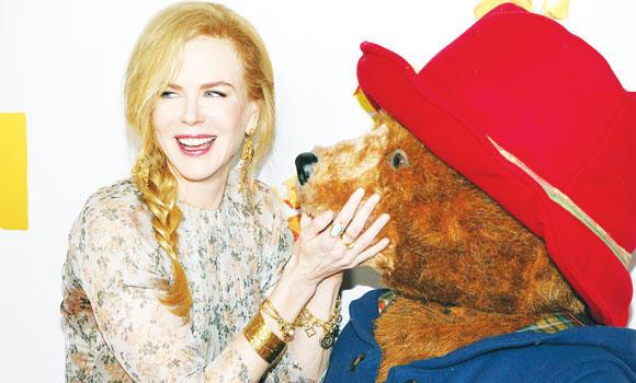 """Actress Nicole Kidman, left, smiles after kissing the character Paddington as she arrives for the Australian premiere of her movie """" Paddington """" in Sydney, Sunday."""
