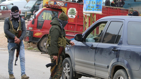 Shiite gunmen check vehicles on a road in the village of Bazzaliyeh which leads the eastern Lebanese town of Arsal in the Bekaa valley, near the border with Syria, as they search for the killer of Lebanese soldier Ali al-Bazaal on Dec. 6, 2014.