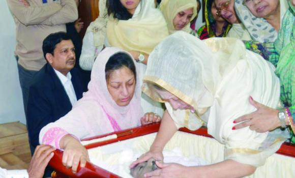 Former Bangladeshi Prime Minister and BNP chief Khaleda Zia, right, mourns over the mortal remains of her son Arafat Rahman Koko lying in state at the BNP office in Dhaka on Tuesday.