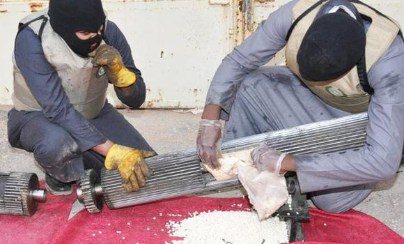Saudi anti-narcotics officers retrieve dangerous drugs hidden in machine parts seized from drug traffickers in this 2014 file photo. (SPA)