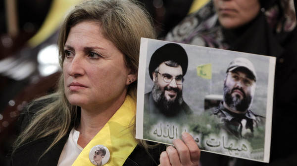 A Hezbollah supporter holds up a portrait of late Hezbollah military commander Imad Mughniyeh (R)and Hezbollah leader Hassan Nasrallah (L) during a recent ceremony makring the death of six Hezbollah fighters in Beirut.