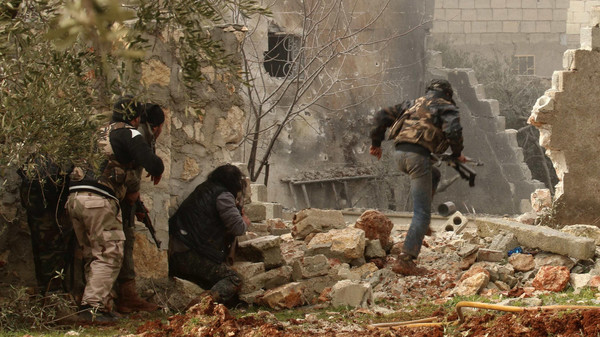 A rebel fighter carries his weapon as he runs while others take positions in Ratian village, north of Aleppo.