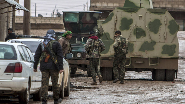 Fighters of the Kurdish People's Protection Units (YPG) walk past an armored vehicle along a street in the town of Tel Tamr February 25, 2015.