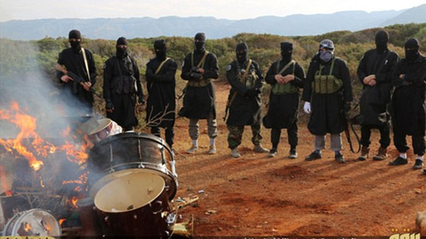 The photos, which were released by an ISIS media wing, show masked militants setting fire to drums and saxophones