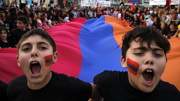 Armenian boys shout slogans against Turkey in front of a huge Armenian flag during a demonstration near the Turkish embassy in central Athens, April 24, 2013.